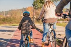 La familia con el montar a caballo del niño monta en bicicleta en la naturaleza fotos de archivo