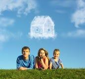 La familia con el muchacho en hierba y el sueño se nublan la casa Fotografía de archivo