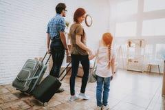 La familia con el niño llegó en el nuevo apartamento brillante fotografía de archivo