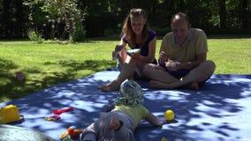 La familia con fin de semana del gasto del bebé en parque y come el helado 4K almacen de video