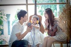 La familia con la niña adentro escucha la música en su teléfono Foto de archivo libre de regalías