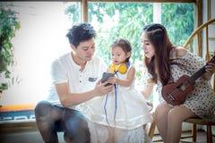 La familia con la niña adentro escucha la música en su teléfono Fotografía de archivo