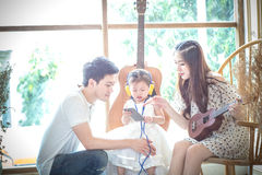 La familia con la niña adentro escucha la música en su teléfono Fotografía de archivo libre de regalías