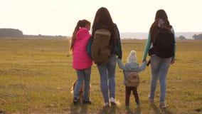 La familia con las mochilas viaja con un perro trabajo en equipo de una familia unida madre, hijas y turistas caseros de los anim almacen de video
