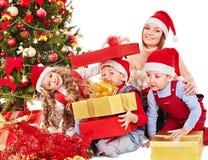 La familia con los cabritos abre el rectángulo de regalo de la Navidad. Imagen de archivo libre de regalías