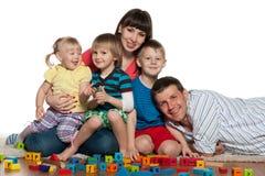 La familia con los niños juega el piso Foto de archivo