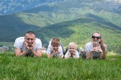 La familia con los niños miente en la hierba Montañas en el backgro Foto de archivo libre de regalías
