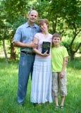 La familia con una biblia en su mano, hombre con la mujer y niño, tres personas en ciudad parquea Fotos de archivo libres de regalías