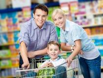 La familia conduce la carretilla de las compras con la comida y el hijo que se sienta allí Foto de archivo libre de regalías