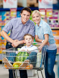 La familia conduce la carretilla de las compras con la comida y el muchacho que se sientan allí Fotografía de archivo