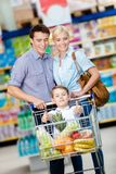 La familia conduce la carretilla de las compras con la comida y el niño pequeño que se sientan allí Fotos de archivo libres de regalías