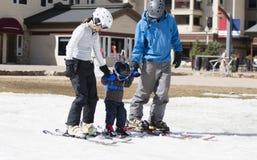 La familia consigue lista para esquiar con el niño pequeño Todos vestidos con seguridad con los cascos imágenes de archivo libres de regalías