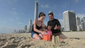 La familia construye el castillo de la arena en el paraíso Australia de las personas que practica surf almacen de metraje de vídeo