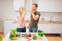 La familia de amor joven del vegano bebe el smoothie natural mientras que cocina verduras crudas en la cocina Detox de la dieta P imagen de archivo