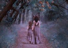 La familia de ciervos está caminando en el bosque, faunos madre y la hija está caminando a lo largo de una trayectoria misteriosa fotografía de archivo