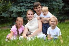 La familia de cinco al aire libre en verano se sienta en hierba fotos de archivo