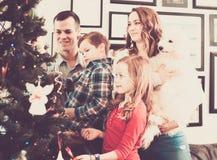 La familia de cuatro miembros adorna el árbol de navidad Imágenes de archivo libres de regalías