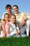 La familia de cuatro miembros al aire libre en verano se sienta en hierba imagenes de archivo