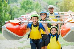 La familia de cuatro miembros feliz en casco y vive chaleco listo para transportar en balsa en el catamarán fotos de archivo