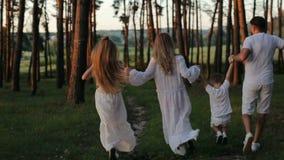 La familia de cuatro miembros feliz joven que se divierte en los padres del bosque y los niños en la ropa y el sombrero de paja b almacen de video