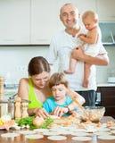 La familia de cuatro miembros junta en una cocina acogedora prepara la comida Fotos de archivo libres de regalías