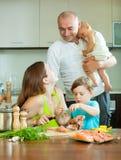 La familia de cuatro miembros juntos en la cocina prepara los mariscos Imágenes de archivo libres de regalías