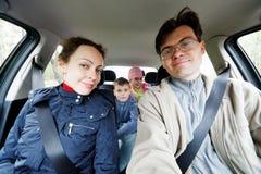 La familia de cuatro miembros se sienta en coche Foto de archivo libre de regalías