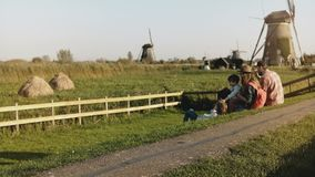 La familia de cuatro miembros se sienta junta cerca de una granja del molino de viento La mamá, el papá y dos niños disfrutan de  metrajes