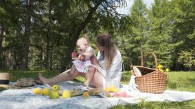 La familia de dos personas, de madre y de hija joven pasando el tiempo junto en el parque de la ciudad para una comida campestre  almacen de video