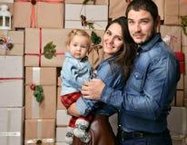 La familia de la Navidad con el niño del bebé en arte rústico presenta Foto de archivo libre de regalías