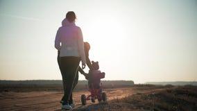 La familia de las siluetas es junta en la puesta del sol Muchacho joven que aprende montar la bicicleta, padre para enseñar a su almacen de video