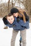 La familia de los jóvenes juega la madera del invierno en nieve Imágenes de archivo libres de regalías