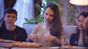 La familia de los niños del grupo de gente come la pizza en un café adolescencias de los niños del primer dentro que comen los al almacen de video
