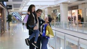 La familia de moda con un niño hace compras en un centro comercial moderno metrajes