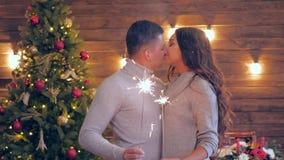 La familia de Navidad, los pares cariñosos jovenes se coloca cerca de uno a con las luces de Bengala en fondo de un árbol de navi almacen de metraje de vídeo