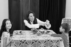La familia de té de consumición de la gente del tres en la tabla Fotografía de archivo libre de regalías