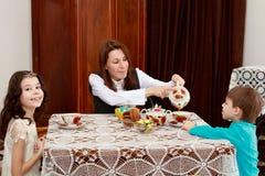 La familia de té de consumición de la gente del tres en la tabla Fotos de archivo libres de regalías