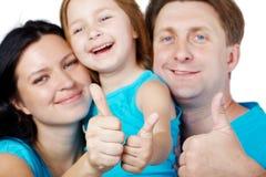 La familia de tres da sus pulgares para arriba Imágenes de archivo libres de regalías
