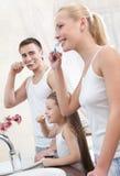 La familia de tres personas aplica sus dientes con brocha Fotografía de archivo