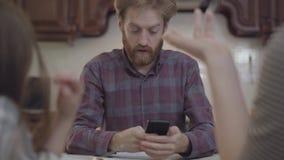 La familia de tres personas que tienen el padre ocupado del desayuno tiene una llamada y un comienzo que habla por el teléfono ce metrajes