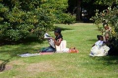La familia del Afro se está reclinando en parque. Imagen de archivo libre de regalías
