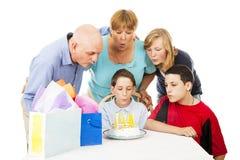 La familia del cumpleaños sopla velas Foto de archivo libre de regalías
