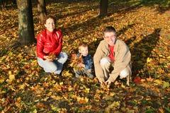 La familia del otoño se sienta Imagenes de archivo