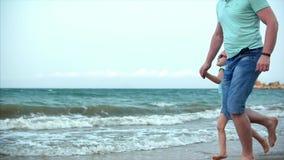 La familia, el padre y la hija jovenes corren a lo largo de la familia feliz de la costa, caminando a lo largo de la costa almacen de metraje de vídeo