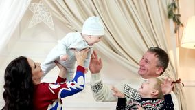 La familia, el papá feliz de la mamá y los niños jugando feliz en la casa, pequeño bebé en las manos en los padres ríe alegre almacen de metraje de vídeo
