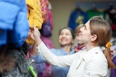 La familia elige desgaste del invierno en la tienda de la ropa Imagen de archivo