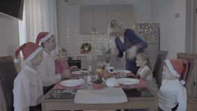 La familia emocionada feliz de seis disfruta de la cena de la Navidad festiva en armosphere acogedor precioso de la celebración d metrajes