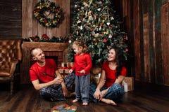 La familia en pijamas juega al lado de un árbol de navidad y de una chimenea Fotos de archivo libres de regalías