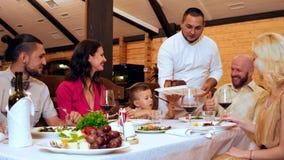 La familia en restaurante, la gran comida y las bebidas alcohólicas en la tabla, un grupo de amigos y los parientes se sientan al almacen de metraje de vídeo