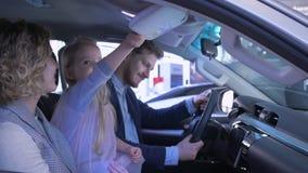 La familia en salón del automóvil, los padres afortunados con la muchacha del niño elige el vehículo y da los pulgares para arrib almacen de metraje de vídeo